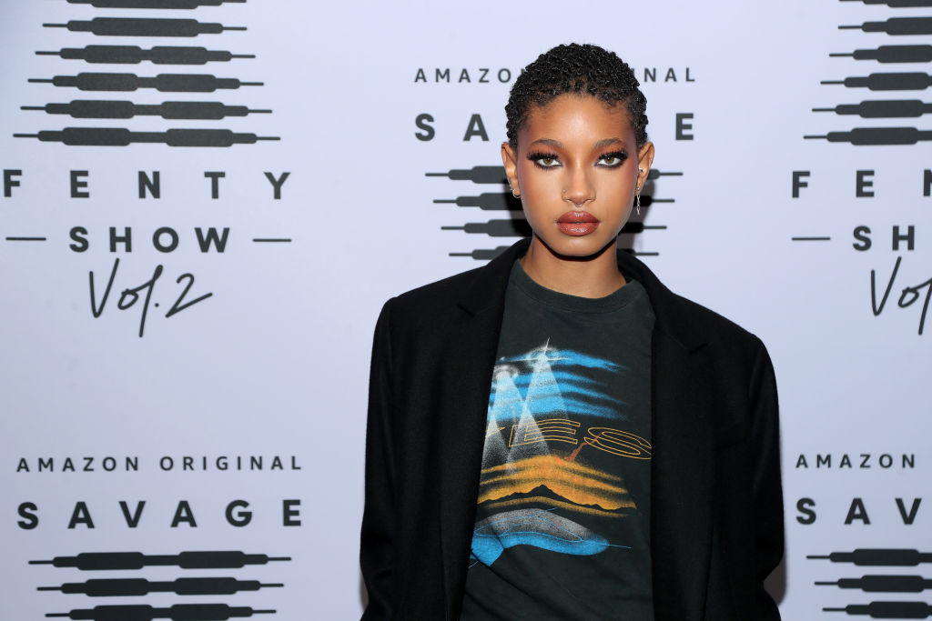 Willow Smith standing in front of a white and black background