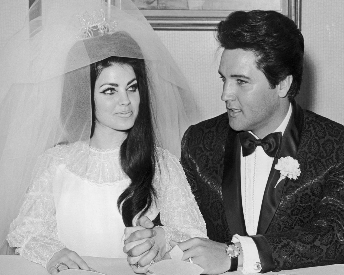 American rock singer and actor 'Elvis Presley (1935 - 1977) sits and holds hands with his wife Priscilla Presley on their wedding day, Las Vegas, Nevada.  She wears her wedding gown and cover.  He wears the carnation of the lapel tuxedo.