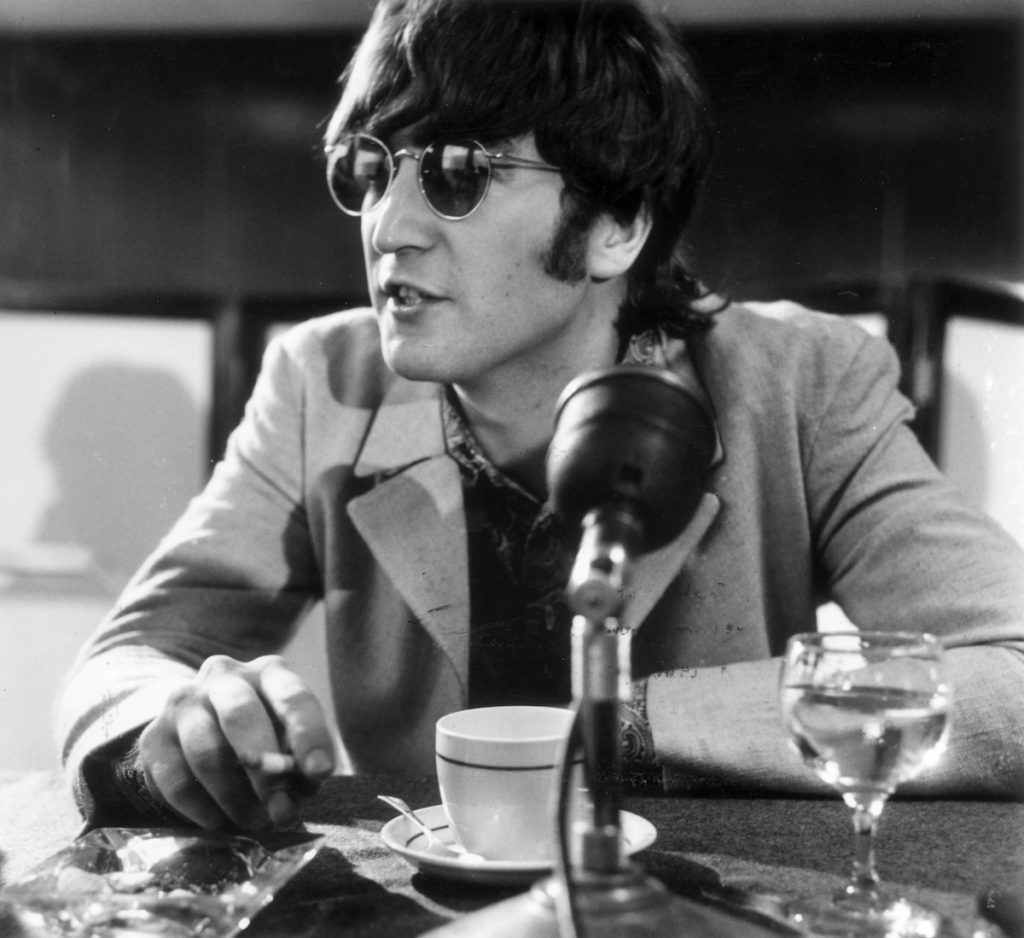 John Lennon (1940 - 1980) at a press conference at London Airport after the Beatles returned from Manila.