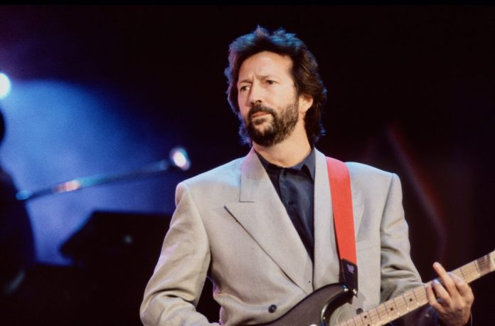 Eric Clapton on stage with a guitar in front of a dark background
