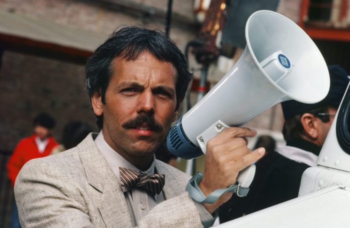Joe Spano as Sgt / LT.  Henry Goldblum holding a megaphone, wearing a jacket and bow tie