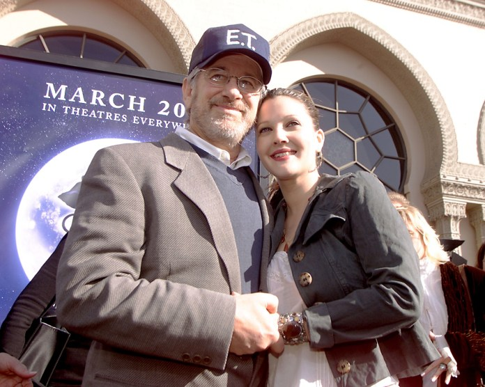Steven Spielberg holding Drew Barrymore in 'ET' baseball cap