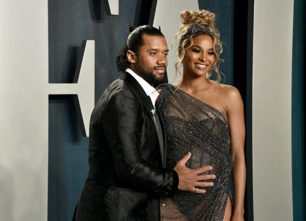 (From left to right) Russell Wilson and Ciara smiling in front of a blue background