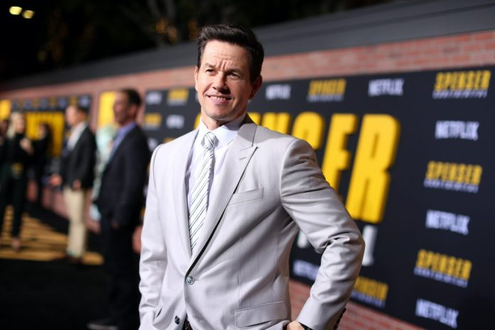 Mark Wahlberg smiling in front of a dark background