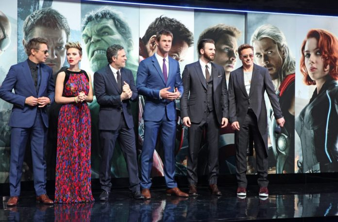 The 'Avengers' films stars Jeremy Renner, Scarlett Johansson, Mark Ruffalo, Chris Hemsworth, Chris Evans and Robert Downey Jr.  They stand in front of a wall that has their MCU characters and are all dressed in formal attire.
