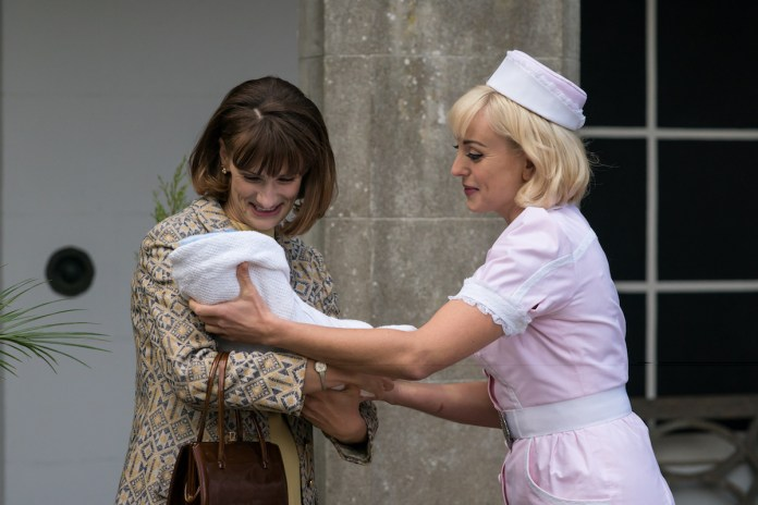 Trixie is reaching for a baby in an episode of 'Call the Midwife' Season 10