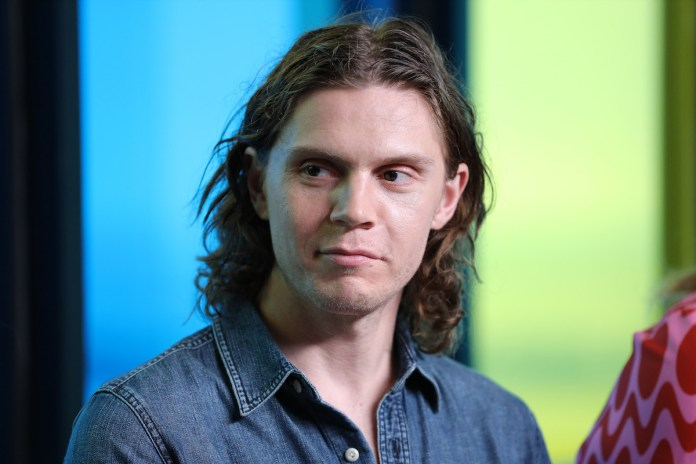 Evan Peters is wearing a denim shirt and smiling away from the camera.