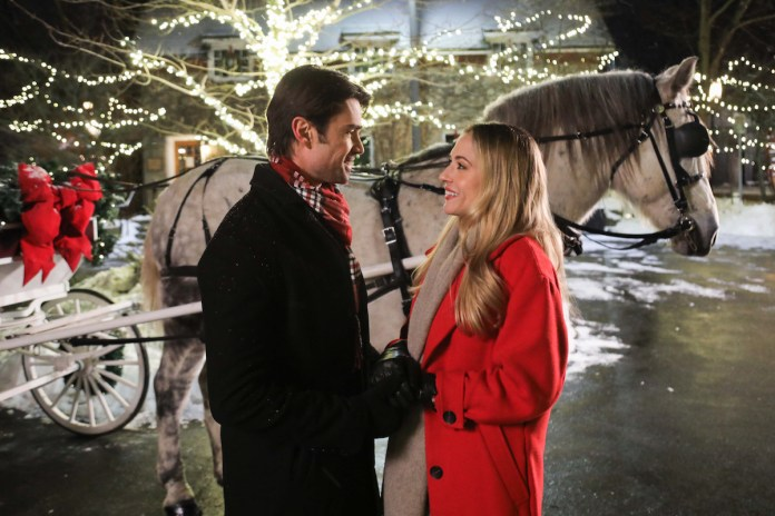 Man and woman standing in front of a horse-drawn carriage in the Lifetime Christmas movie 'It Takes a Christmas Village'