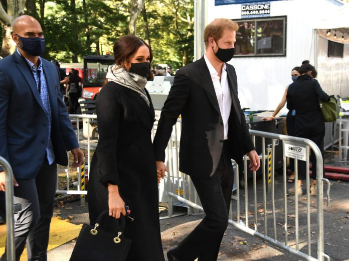 Meghan Markle and Prince Harry arrive at Global Citizen Live holding face masks and hands
