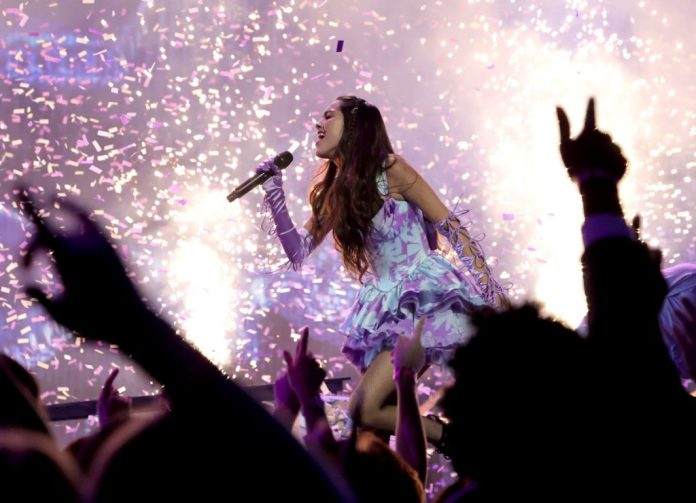 Olivia Rodrigo takes to the stage at the VMAs in a little purple dress surrounded by fall confetti.