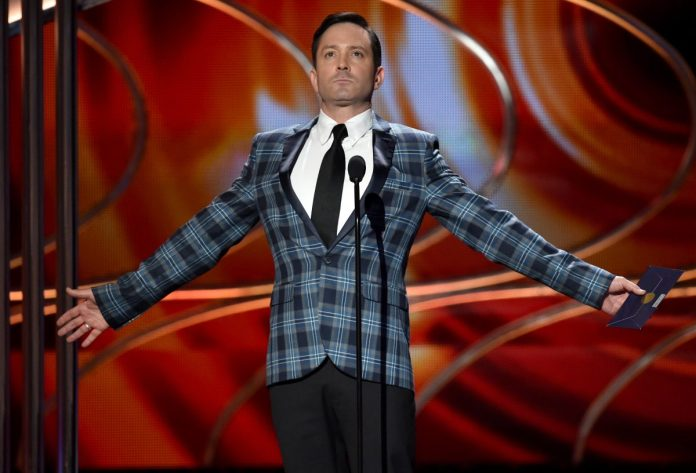 'Supergirl' actor Thomas Lennon wears a blue plaid suit on stage at an awards show.