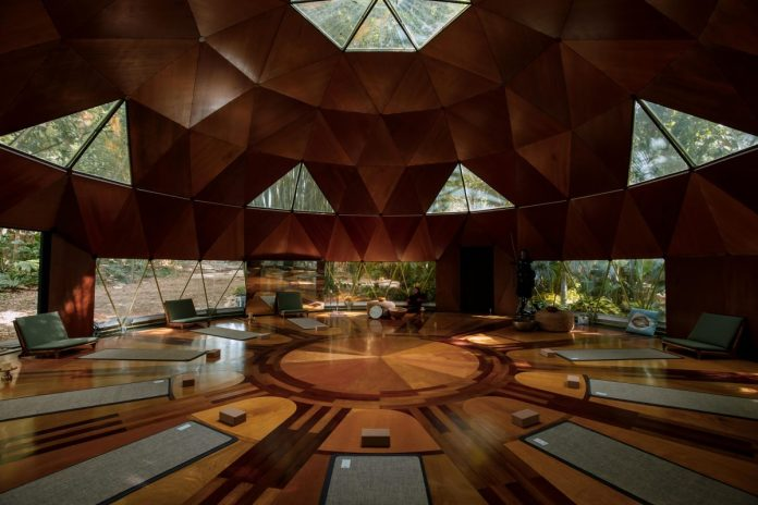 A large yoga/meditation room with large glass windows at Tranquillum House.  Nine mats are placed on the floor waiting for the guests.