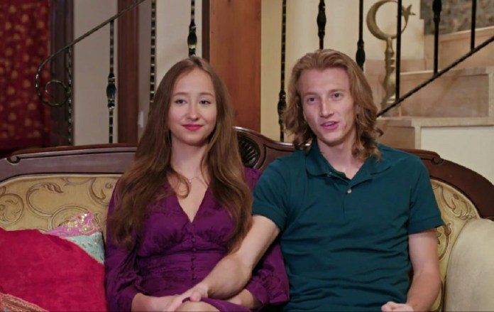 Alina and Steven on '90 Day Fiancé: The Other Way - Alina is wearing a purple dress, Steven a green polo.  They sit on a couch in front of the camera.  Steven's hand is on his knee.
