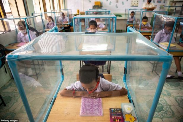 A Thai student prepares for his lesson at school while at a desk with a protective screen
