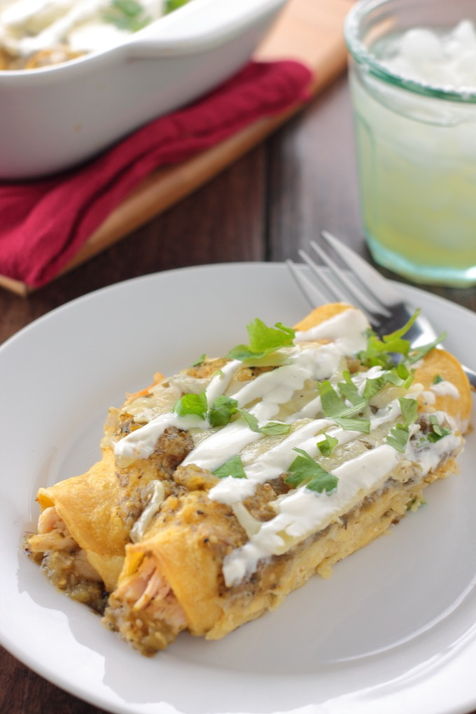 Chicken Enchiladas Verdes - A cheesy pan of chicken enchiladas with a tangy tomatillo green sauce can be on your dinner table in 30 minutes. Plenty of time for a margarita!