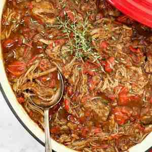 brown lamb ragu with red capsicum in a red pot