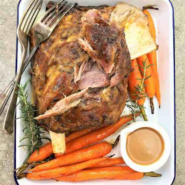 roasted lamb shoulder in a white baking dish with carrots and gravy