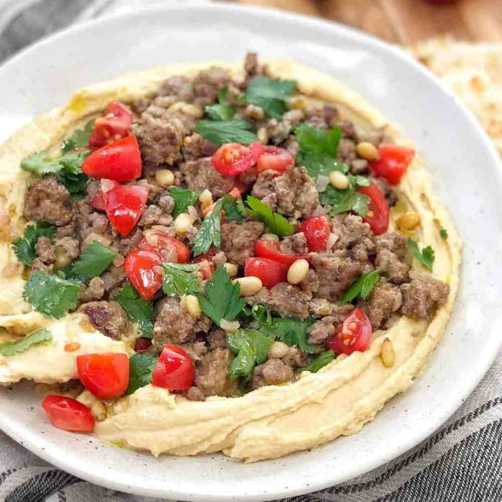 moroccan lamb mince, tomatoes and herbs on a pile of hummus on a white plate