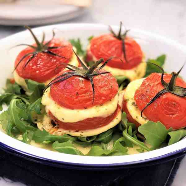 baked mozzarella tomatoes with basil pesto and rocket arugula