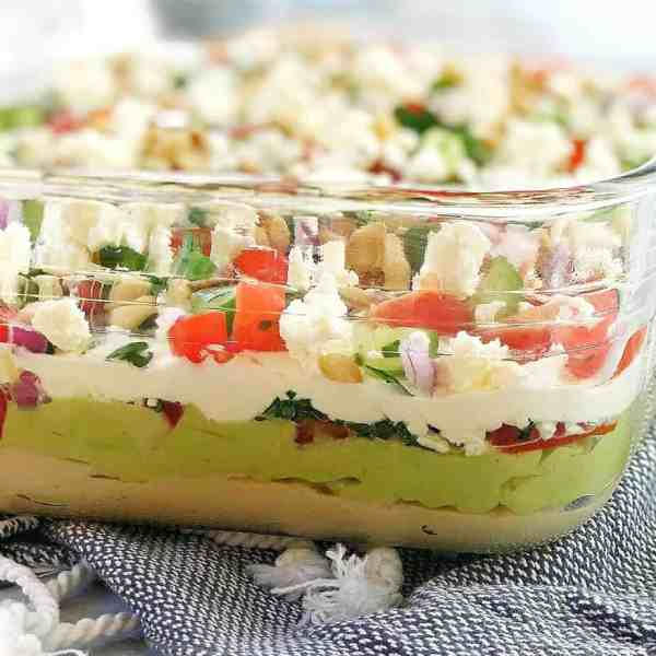 Side view of glass dish with layers of avocado, sour cream, hummus and salad