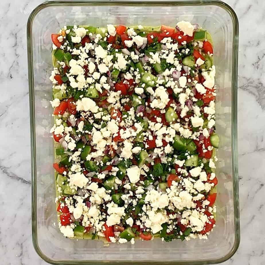 feta, parsley, cucumber, tomato on top of mashed avocado layer in a glass dish