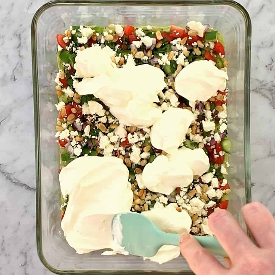 dollops of sour cream on top of chopped greek salad ingredients in a glass bowl
