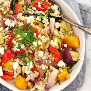 brightly coloured roasted vegetables mixed with white pearl couscous in a white bowl