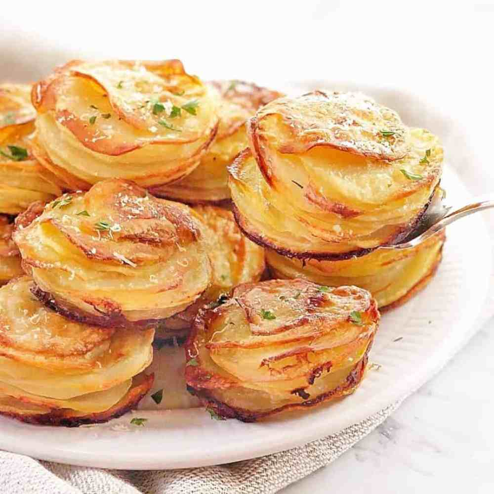 stacks of cooked sliced potatoes on a white plate