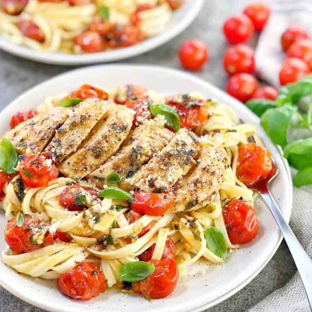 pasta on white plate with chicken breast and red cherry tomatoes on top
