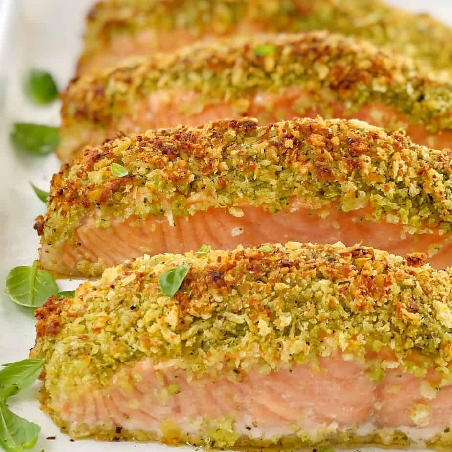 Pieces of cooked salmon topped with pesto crust sitting on a white baking tray