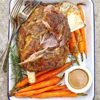 lamb shoulder roast and carrots on a white baking tray
