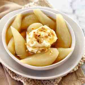 sliced pears in a white bowl with syrup and nuts on top