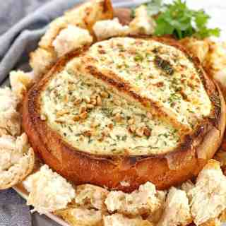 hollowed out bread loaf filled with dip with chunks of bread surrounding