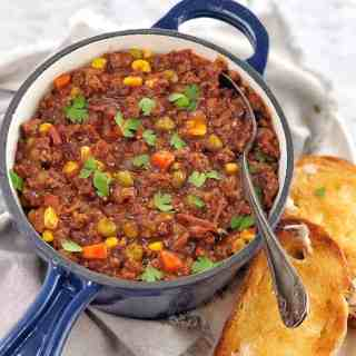mince and vegetables in a blue saucepan with slices of toast on the side
