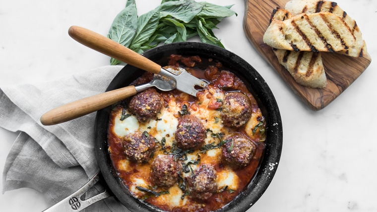 Close up image of spicy meatballs in a skillet with melted cheese, serving utensils, fresh basil, and two slices of grilled bread