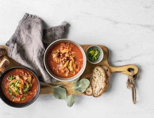 Overhead of two bowls of cabbage roll stew on a long wooden board with a napkin and slices of bread