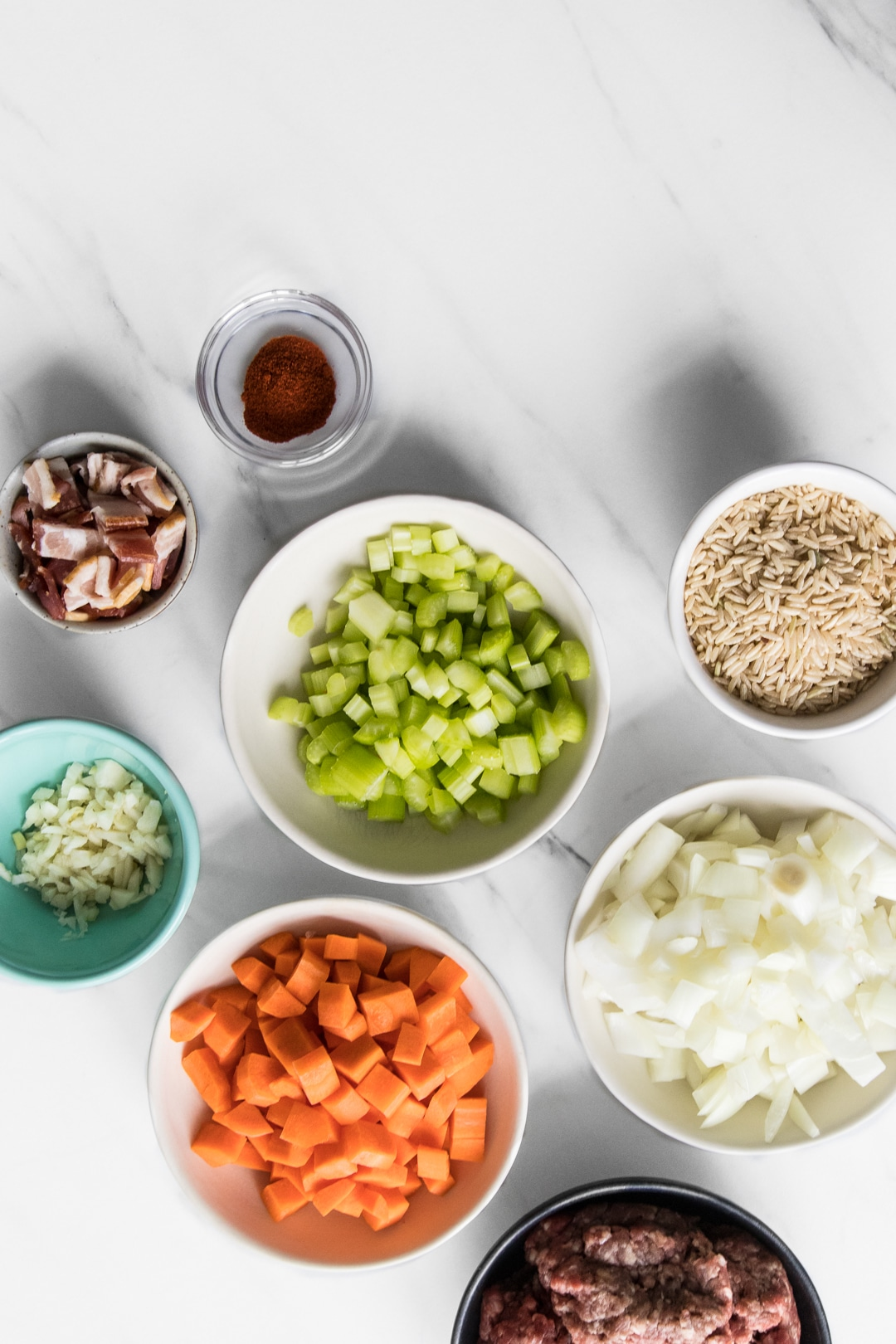Close up photo of prepped ingredients for Cabbage Roll Stew. Ground beef, carrots, garlic, bacon, celery, rice and onions