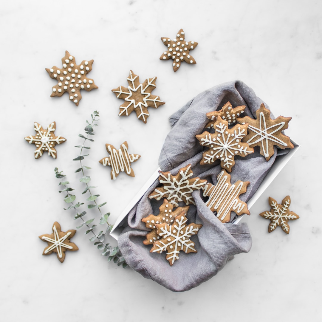 Holiday Cookie Recipes Gingerbread Snowflakes on white marble and in white box with grey napkin