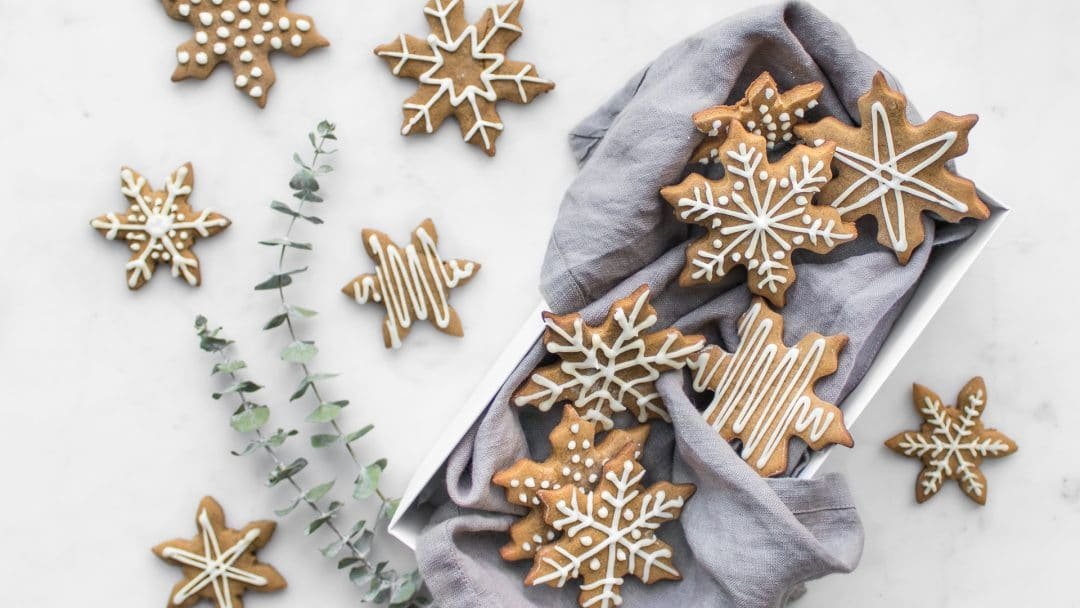 Snowflake shaped gingerbread cookies decorated with white icing laying on napkin and white marble