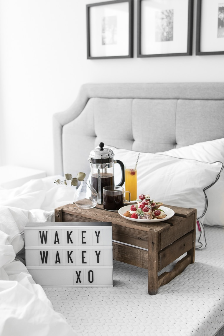 """""""Wakey Wakey XO"""" on small cinema sign laying on an Endy mattress with a cup of coffee, french toast, a newspaper, and two Endy pillows"""