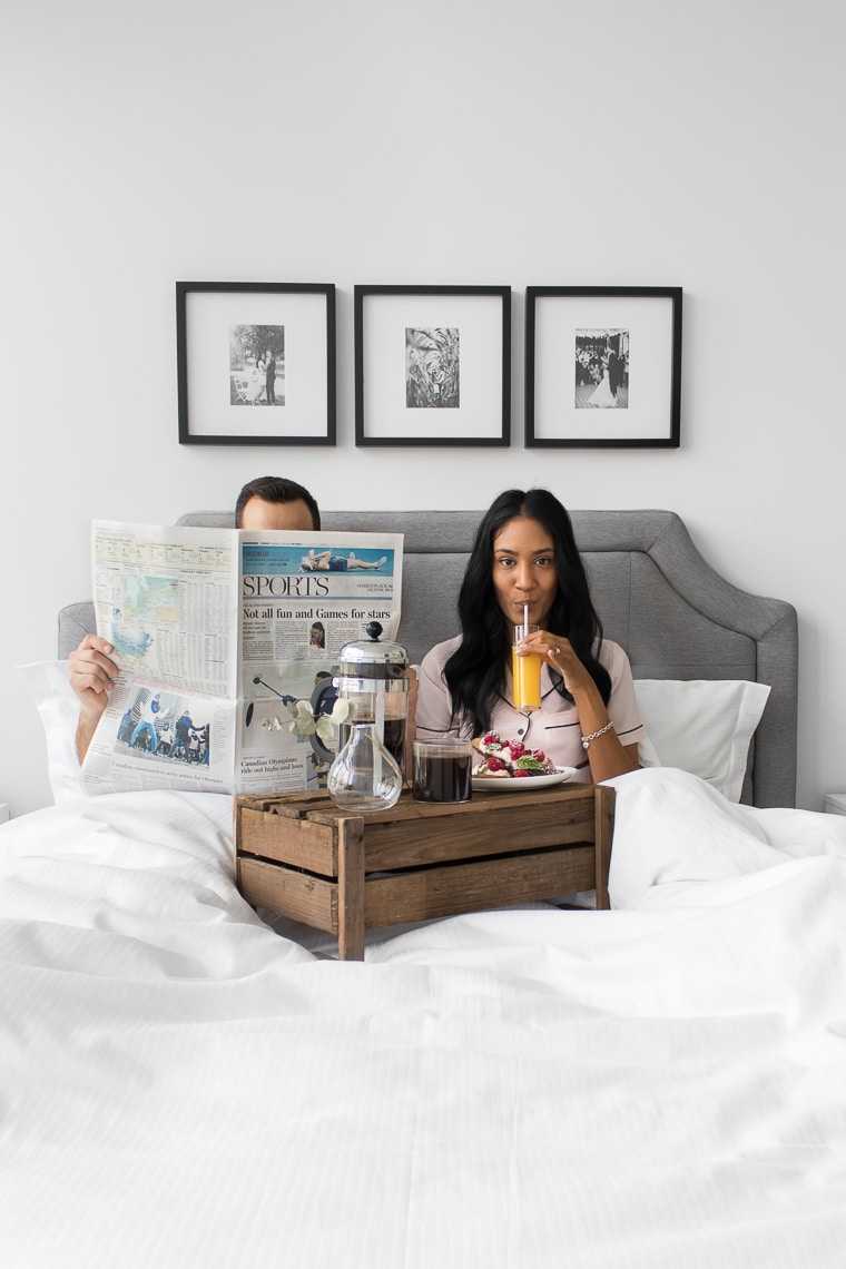 Philip reading a newspaper with his head poking above and Mystique sipping on orange juice looking at the camera while sitting up in bed behind a wooden crate with french toast and coffee.