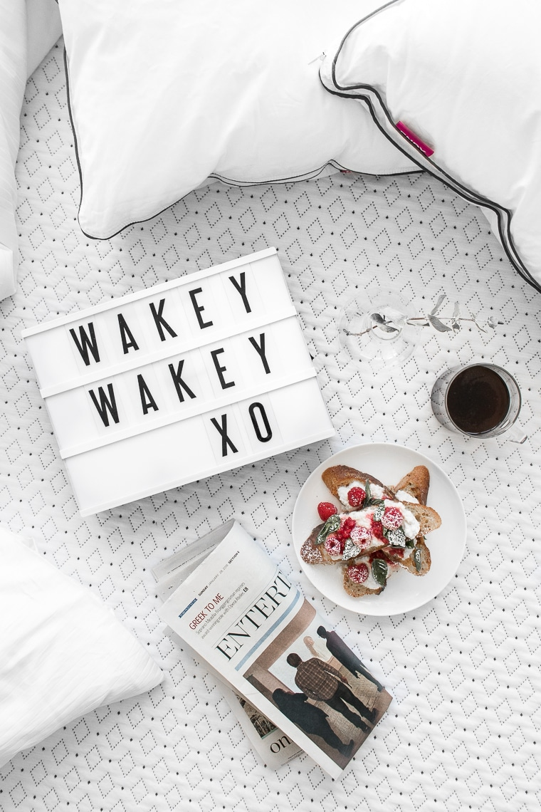 """Overhead of """"Wakey Wakey XO"""" on small cinema sign laying on an Endy mattress with a cup of coffee, french toast, a newspaper, and two Endy pillows"""