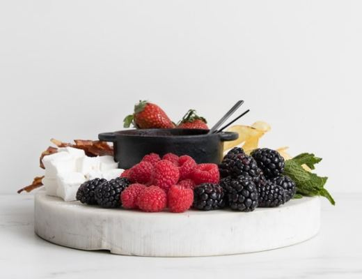 Side view of marble slab with raspberries, blackberries and marshmallows, with a small cast iron pot with dark chocolate fondue for two