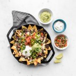 Loaded nachos in a cast iron pan with bowls of guacamole, salsa, and sour cream