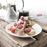 French toast with maple ricotta, raspberries and basil styled on a white plate on a wooden crate
