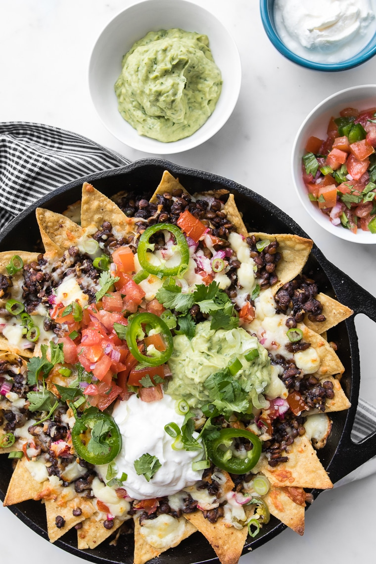 Fresh baked loaded nachos in a cast iron skillet with bowls of guacamole, sour cream and salsa