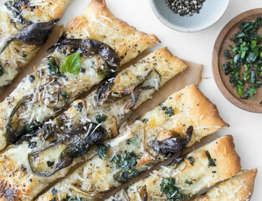 Sliced Cacio e Pepe Pizza with Spring Ramps next to plate of basil and black pepper
