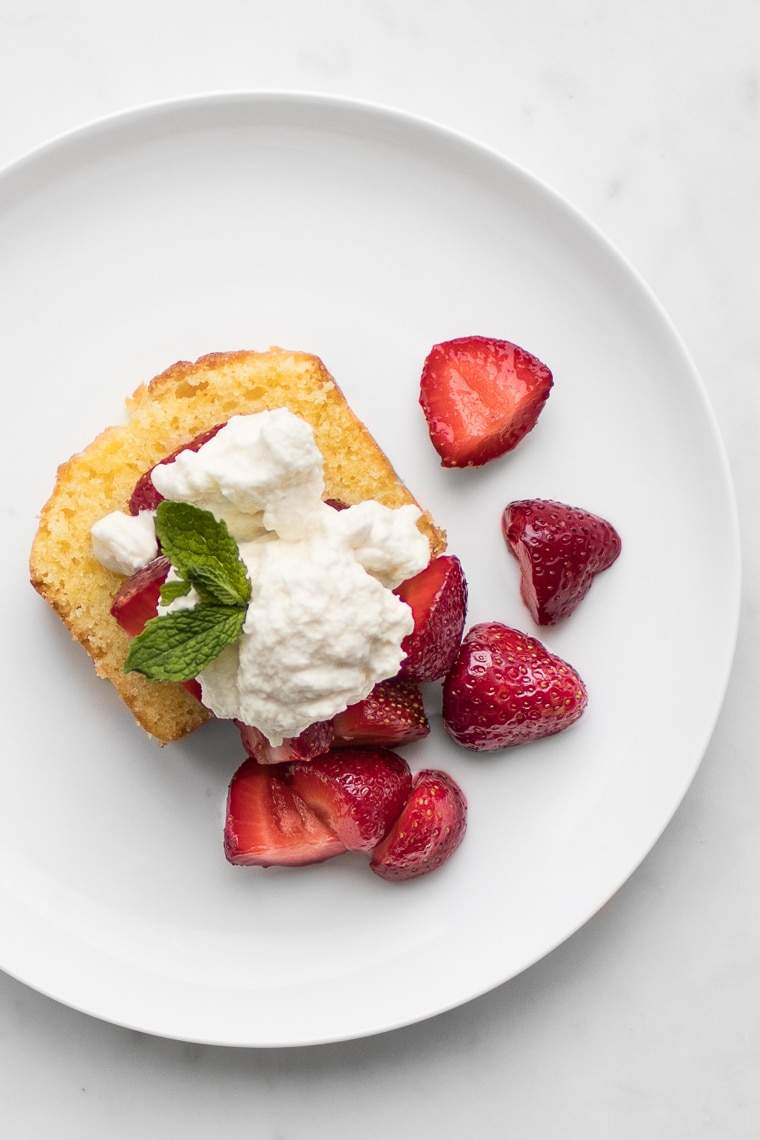 Slice of Strawberry Shortcake Cake with Mascarpone Cream and Strawberries on a white plate