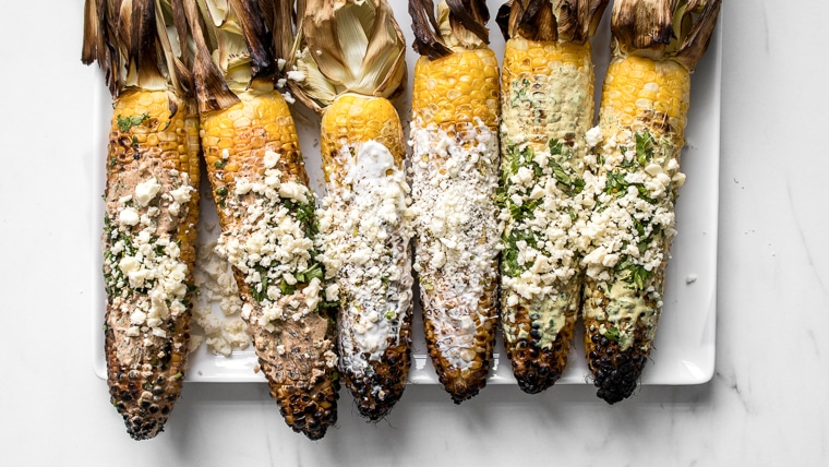 A plate of grilled street corn with husks attached served 3 different ways