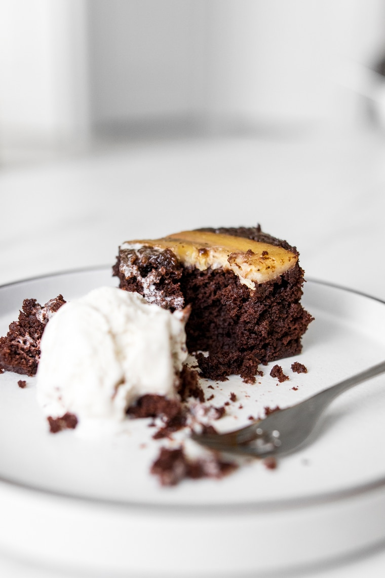 A slice of chocolate banana cake with ice cream and partially eaten